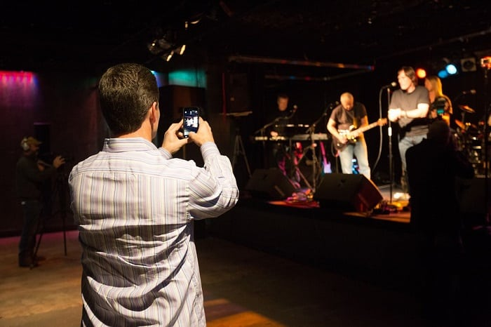 man filming concert