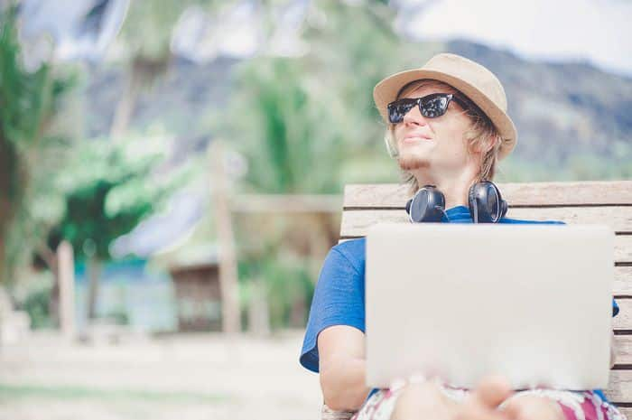 man working on laptop at the beach
