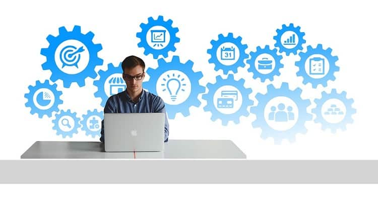 Person sitting in front of a laptop with gears in the background
