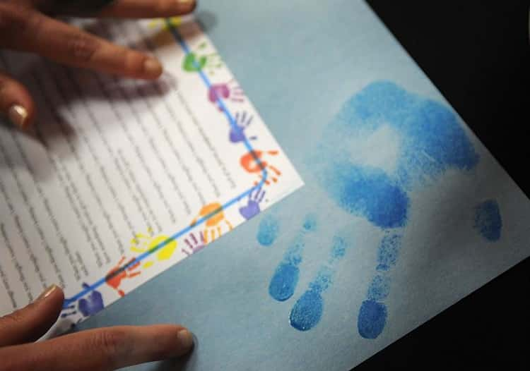 Person touching a paper with hands painted on it