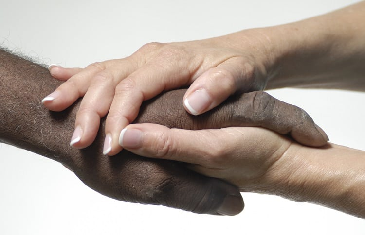 White person touching an African American person's hands