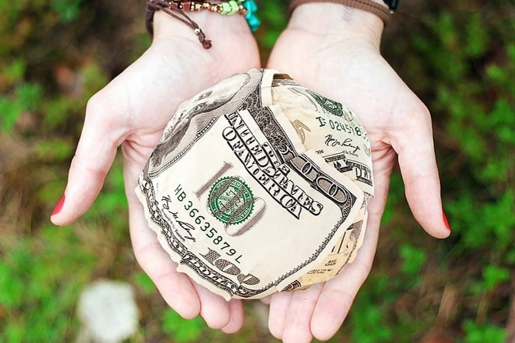 Hands offering a ball made of dollar bills