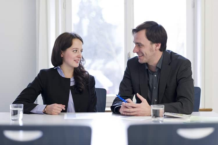 Two people sitting at a desk during an interview