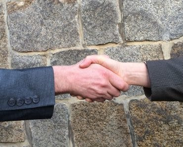 People shaking hands outside, after a successful negotiation