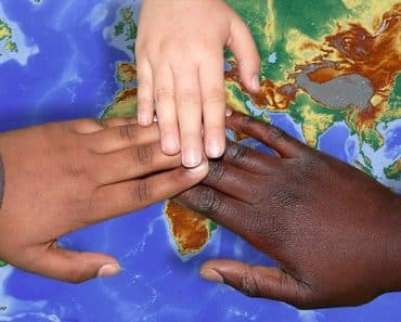 People of different color touching their hands above a world map