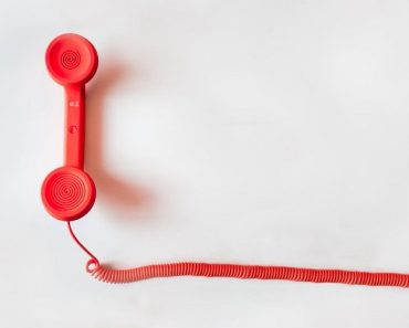 Red phone handset on a white surface