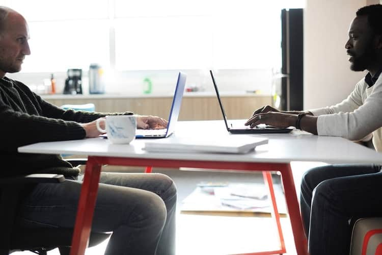 Two people sitting at a desk negotiating