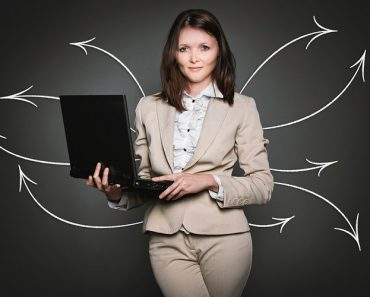 Woman holding a laptop with some arrows drawn around her