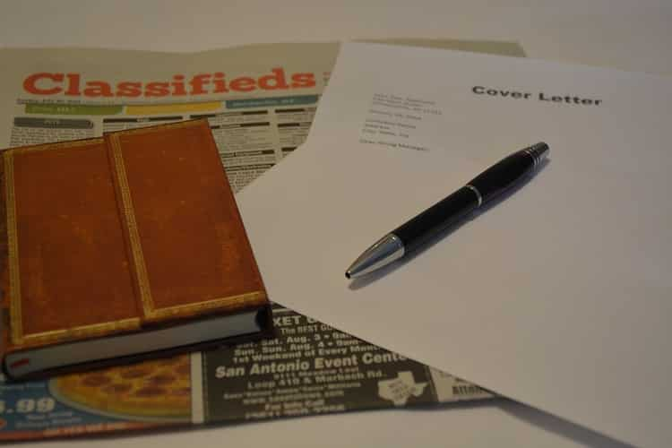Cover letter template placed on a newspaper next to a diary