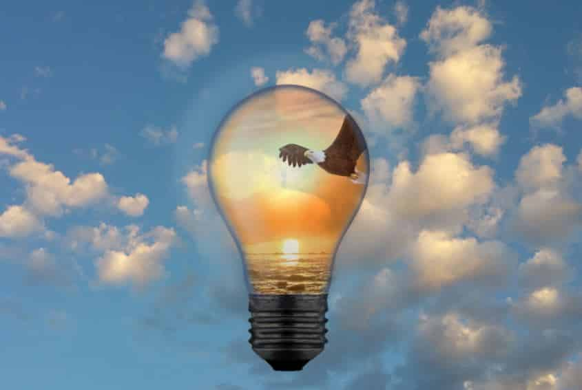 getting a patent starts with an idea, picture is a light bulb against the blue sky, containing an eagle in flight in front of a sunset background