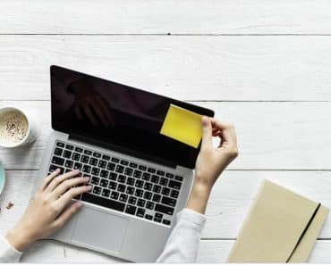 Being productive is important when working from home can be done like this woman with a laptop, yello sticky note and snack working at home.