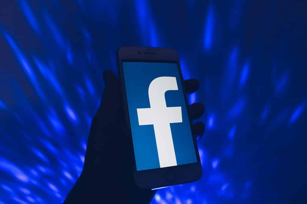 A hand holding a smartphone with the Facebook icon.