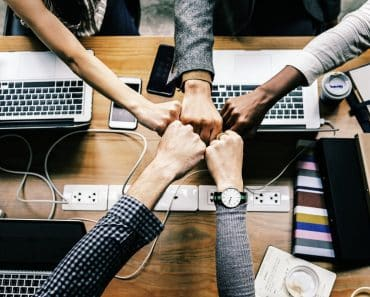 Work team fist bumps: employee engagement means teamwork