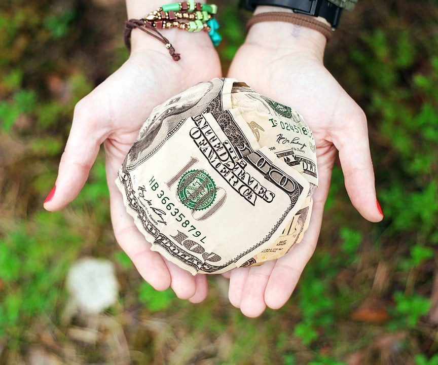 A woman holding her hands out with a ball of crowdfunding cash.