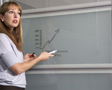 Woman teaching while pointing on the board