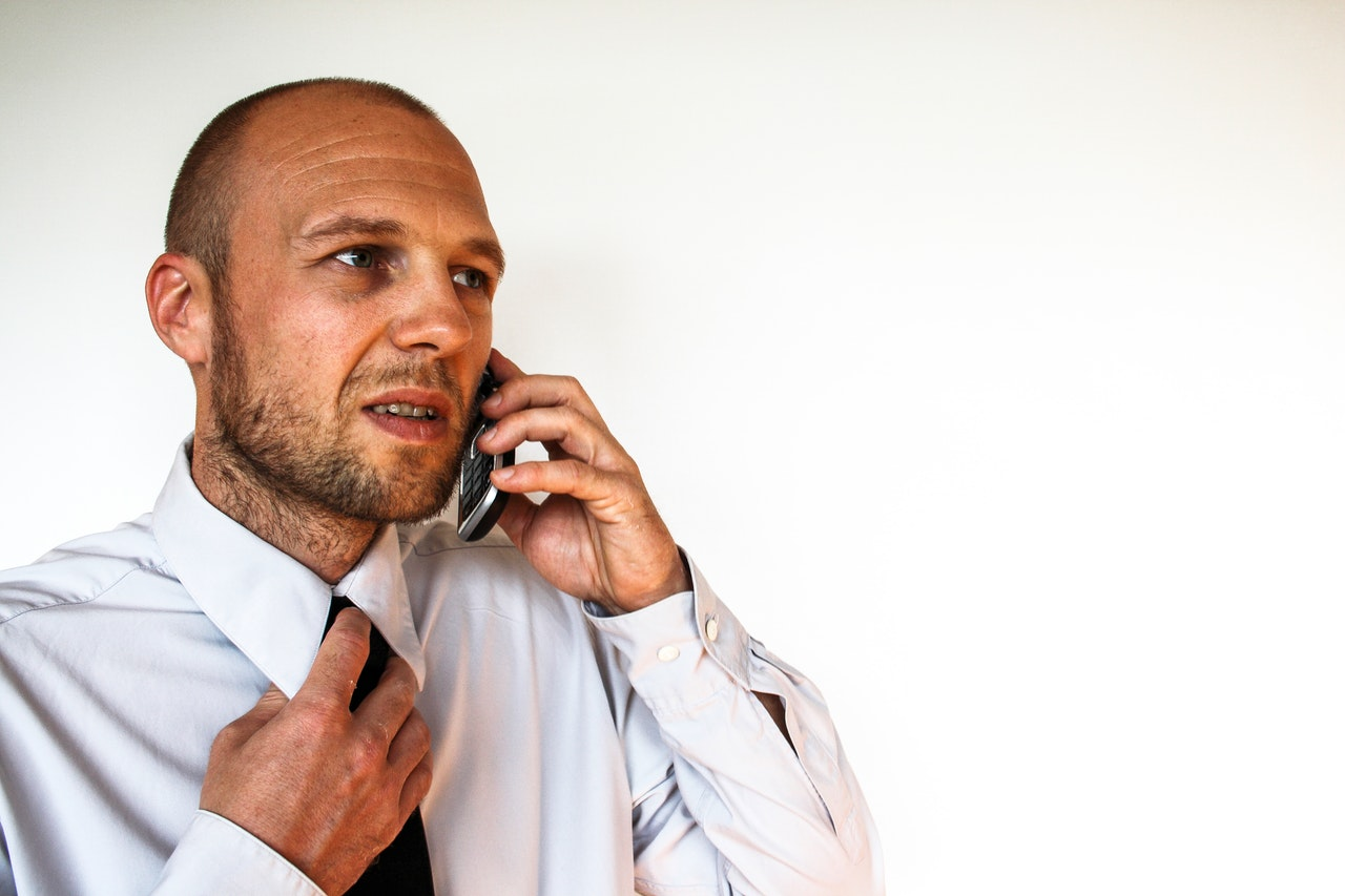 Man wearing white shirt talking to someone on a phone