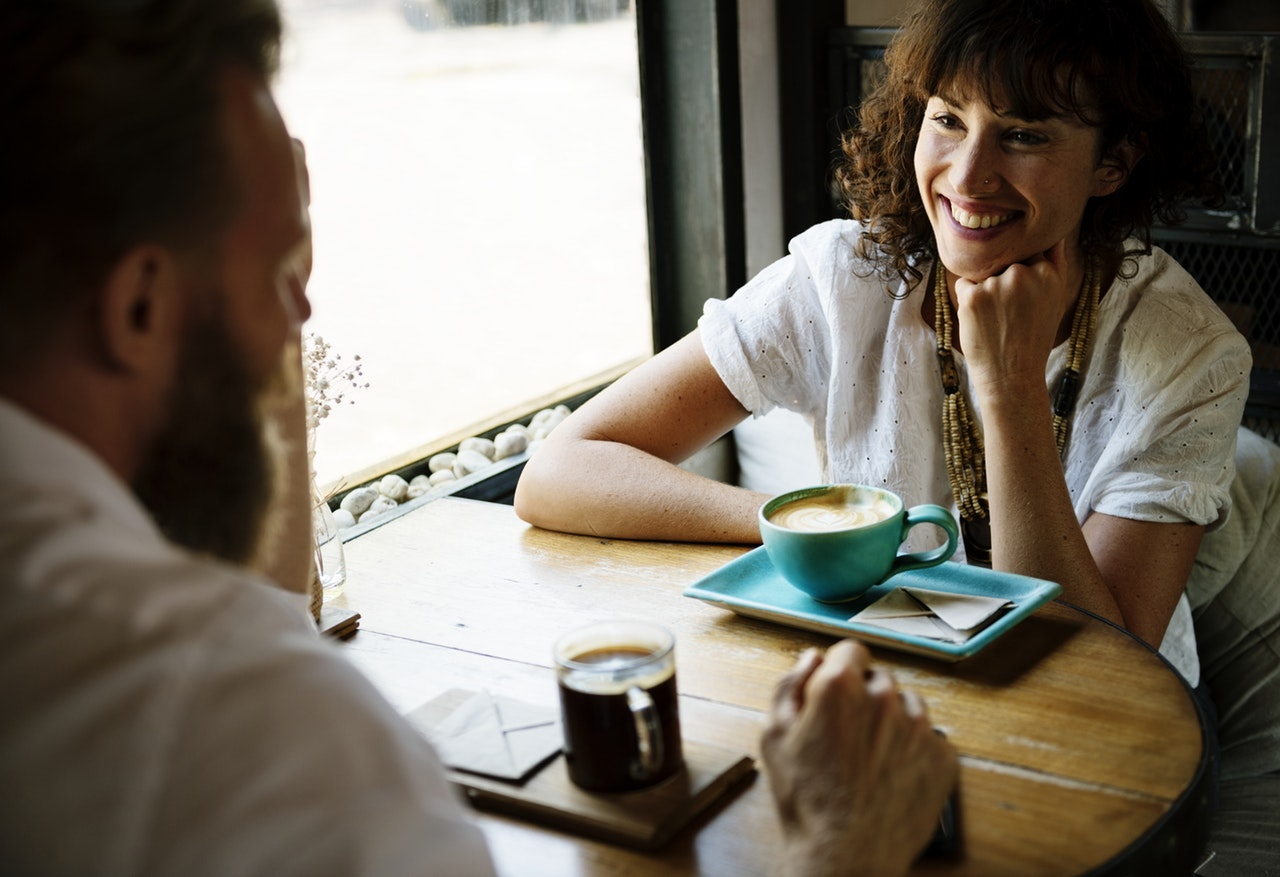 Woman talking to a man in a cafe