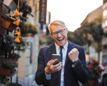Happy man while looking at his phone