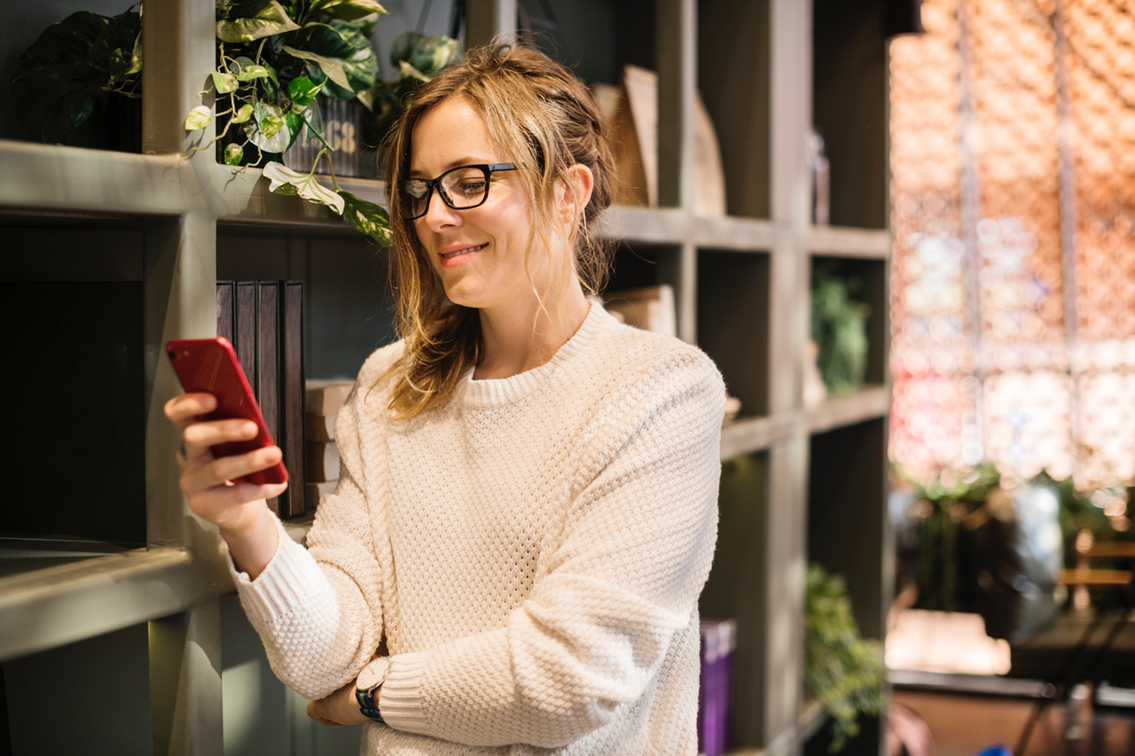 Woman using smartphone beside bookshelf